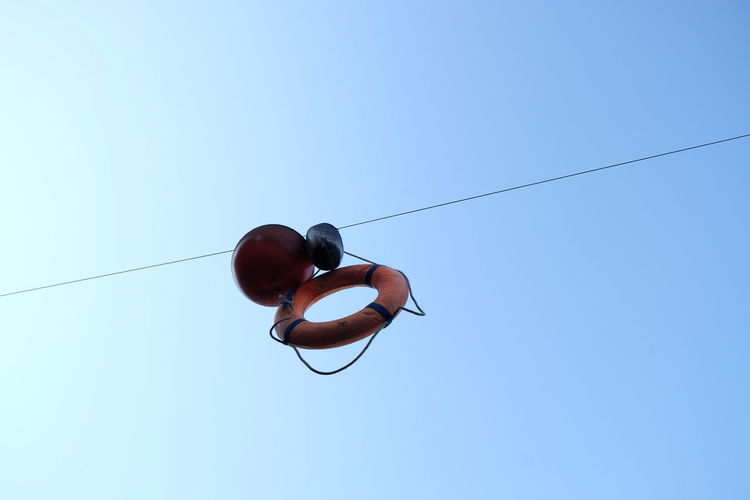 Low angle view of life belt hanging against clear blue sky
