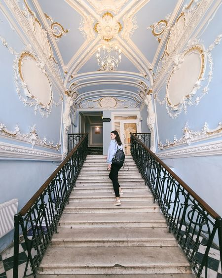 Woman standing on staircase against building