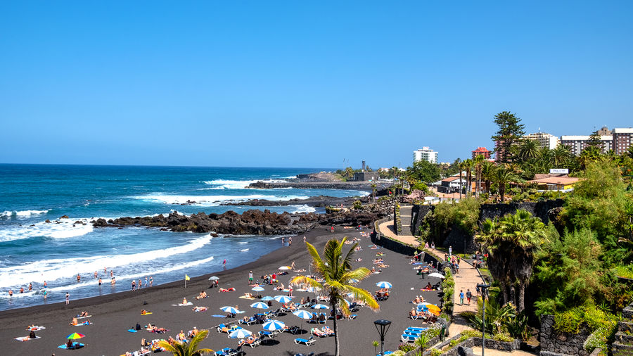 """Playa Jardin - Puerto de la Cruz one of the most beautiful beaches in Tenerife. The beach """"Playa Jardin"""", a black sandy beach, is located in the north of Tenerife in Puerto de la Cruz. Puerto De La Cruz Tenerife Teneriffa Playa Jardin SPAIN Canary Islands Atlantic Ocean Water Sea Beach Land Sky Nature Clear Sky Architecture Tree Plant Building Exterior Day Copy Space Blue City Built Structure Horizon Horizon Over Water High Angle View Outdoors"""