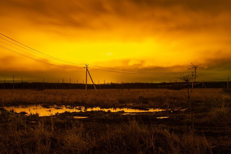 Electricity pylon on field against romantic sky at sunset