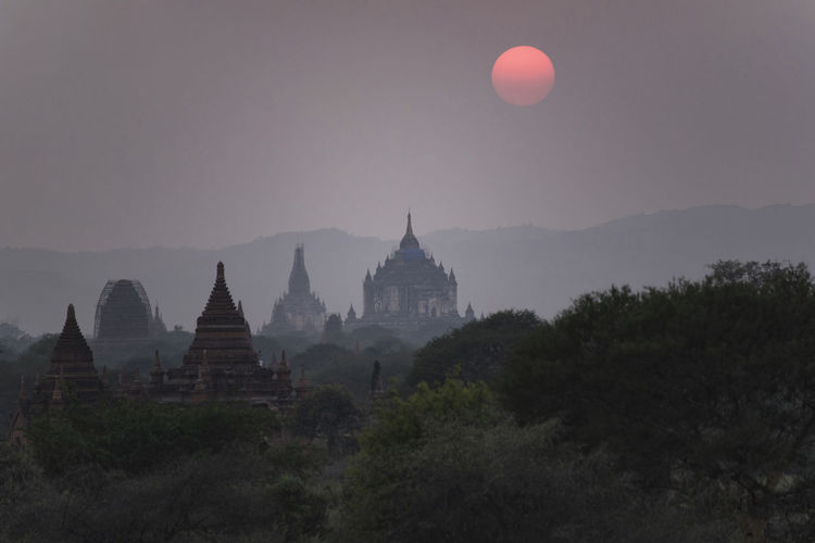 Temple amidst trees against sky at sunset