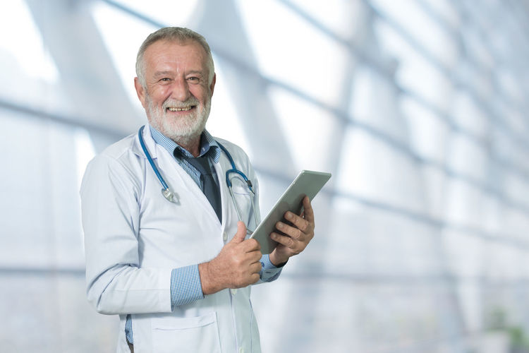 Caucasian, Doctor  Healthcare Hospital Man Office Standing Tablet Uniform Work Clinic Computer Consulting Diagnose Elderly Electronics  Expert Male Medical Physician Professional Senior Smiling Stethoscope  Technology