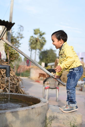 Boy playing with hand pump in village