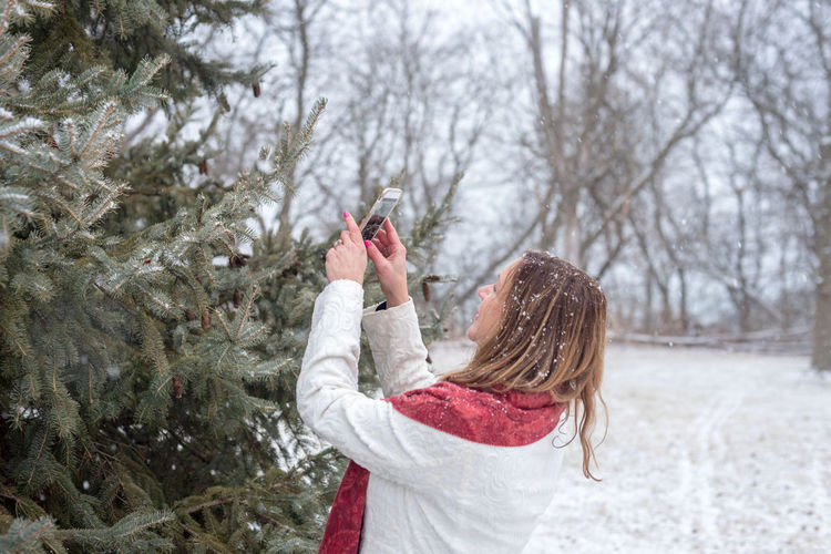Woman photographing tree during winter