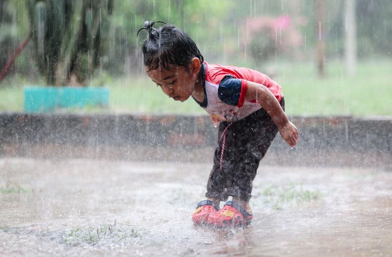 Boy Playing Outdoors During Rainy Season
