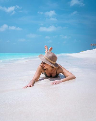 Female on white sand beach in maldives