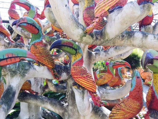 A bird sculpture display in the garden Multi Colored Outdoors Sculpture Bird Sculpture Garden Garden Sculpture