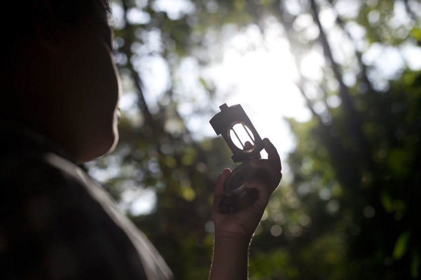 Finding Right Way with Compass Boys Childhood Close-up Compass Direction Focus On Foreground Forest Holding Human Hand Leisure Activity Navigation Navigational Compass Navigational Equipment One Person Outdoors People Photography Themes Tree Young Adult