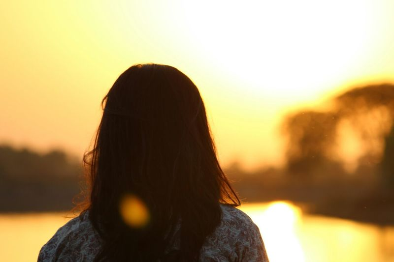 Rear view of woman during sunset