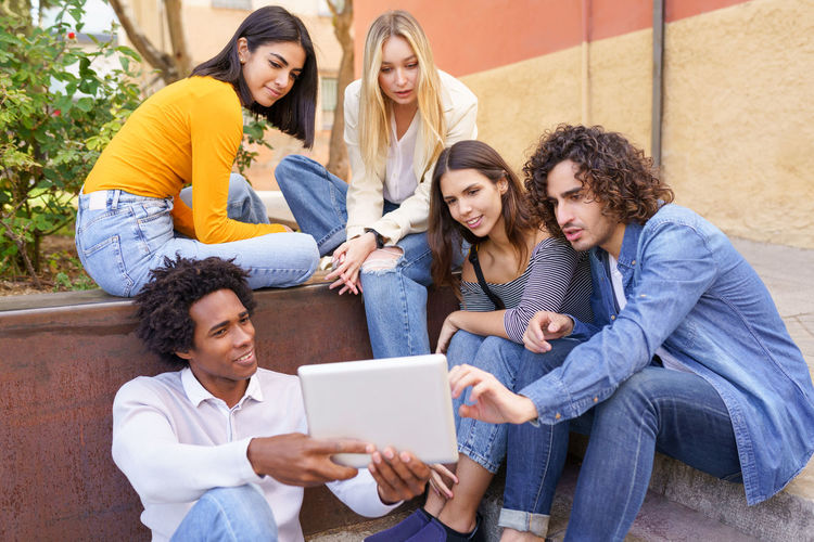 Friends looking away while sitting on mobile phone