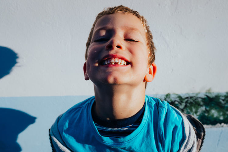 Portrait of smiling boy against wall