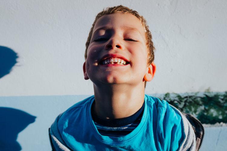 Portrait of smiling boy against wall