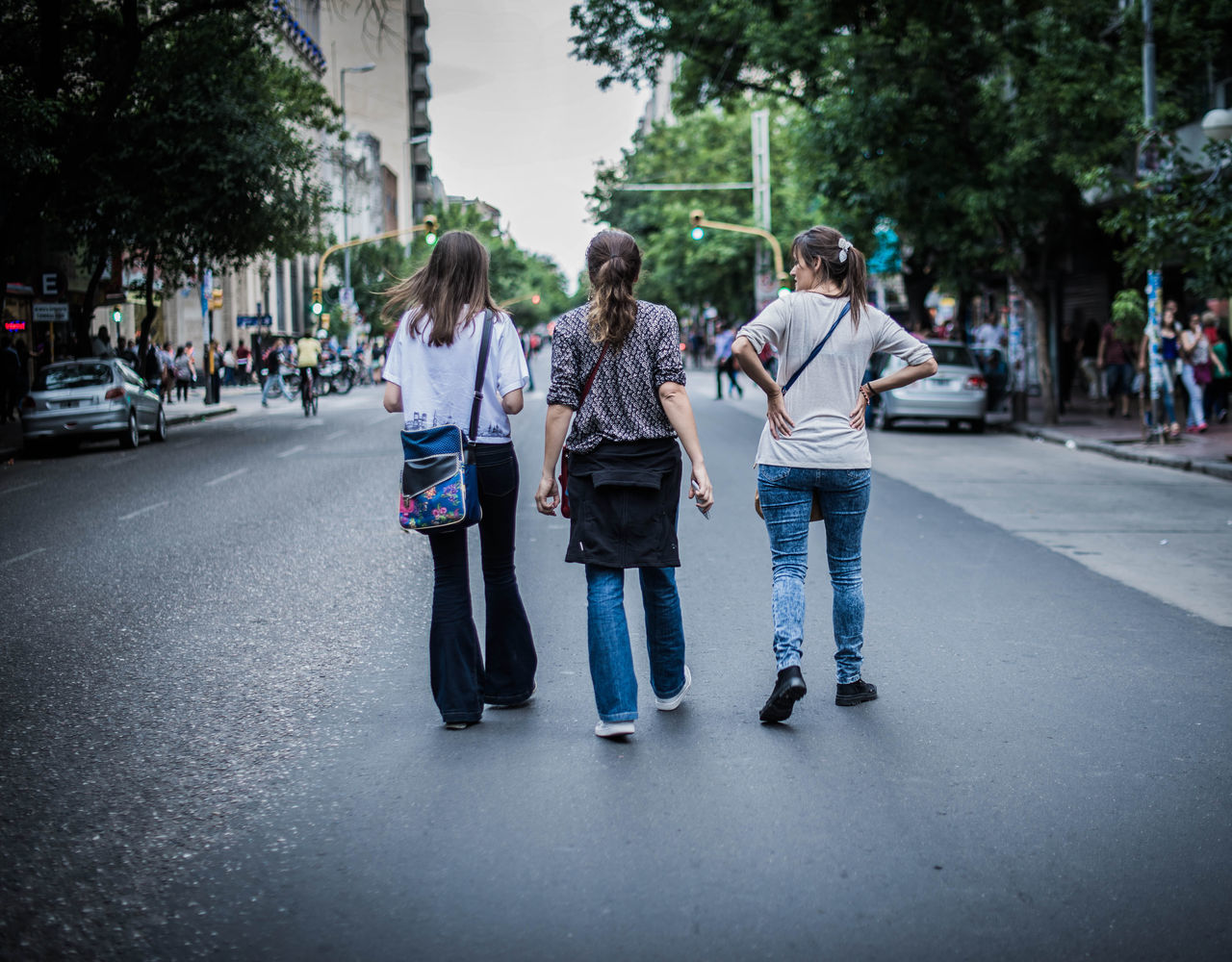 full length, casual clothing, day, street, real people, outdoors, togetherness, front view, road, walking, transportation, tree, leisure activity, young adult, young women, women, lifestyles, friendship, wireless technology, building exterior, technology, adult, people, adults only