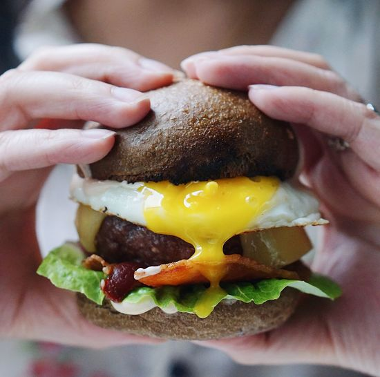 Close-Up Of Hand Holding Burger In Plate