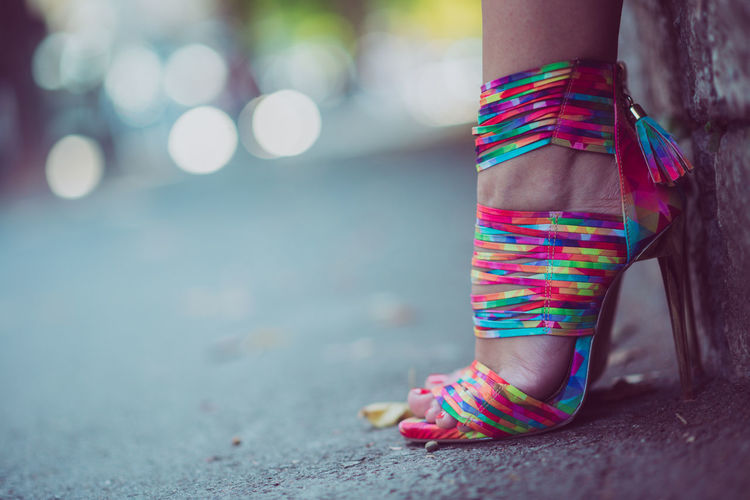 Low section of woman wearing colorful high heels