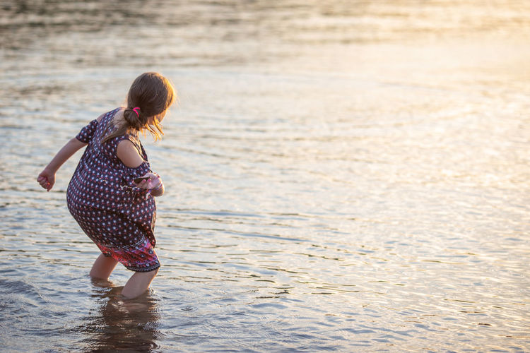 Ankle Deep In Water Beach Casual Clothing Child Childhood Day Females Full Length Girls Golden Hour Hairstyle Land Leisure Activity Lifestyles Nature One Person Outdoors Real People Rear View Sea Skipping Rocks Standing Water Women