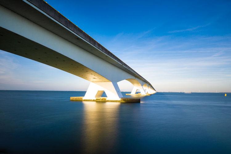 View Of Bridge Over Sea Against Blue Sky