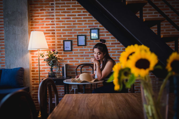 Woman sitting on table at sidewalk cafe
