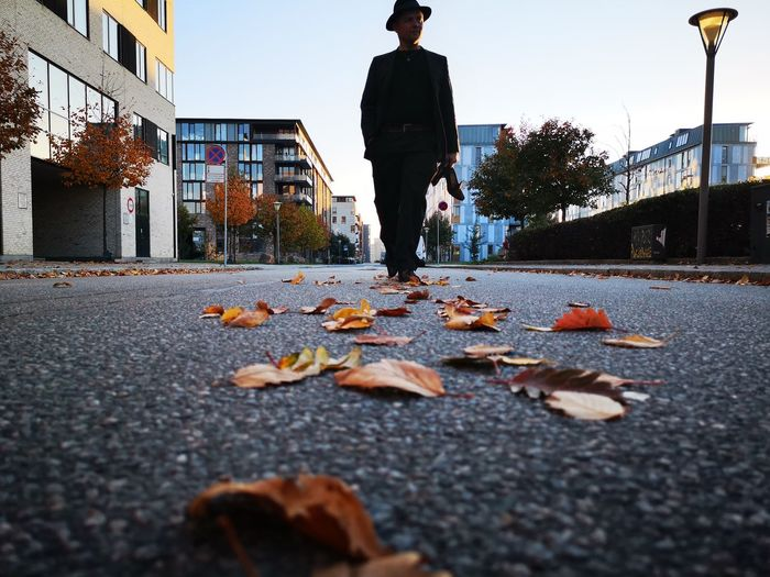 Man walking on leaves in city