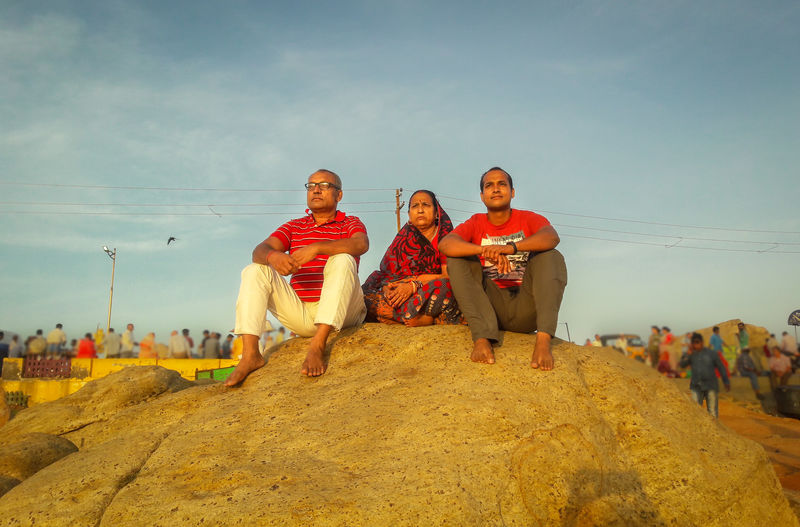 Low angle view of parents with son sitting on rock against sky