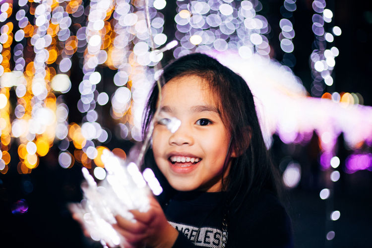 Close-Up Portrait Of Smiling Girl Holding Illuminated String Lights At Night