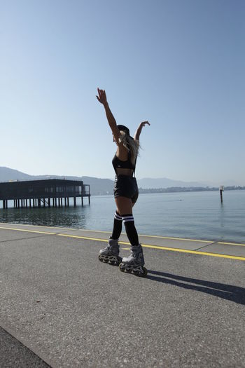 Woman inline skating on road by sea