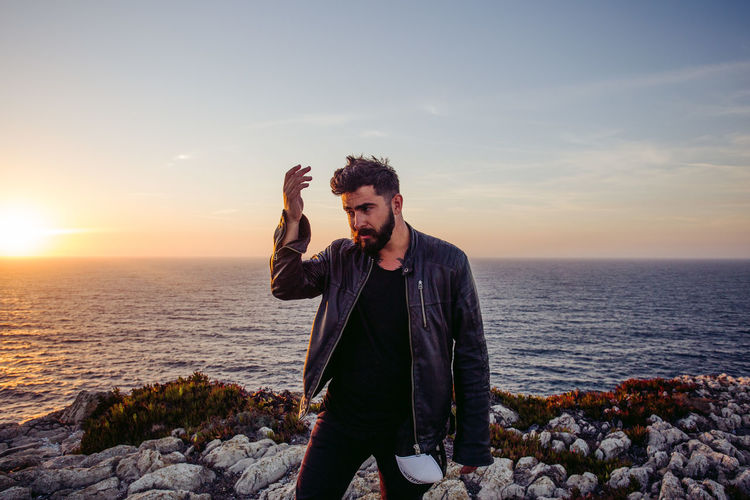 Mid adult man gesturing while standing by sea against sky during sunset