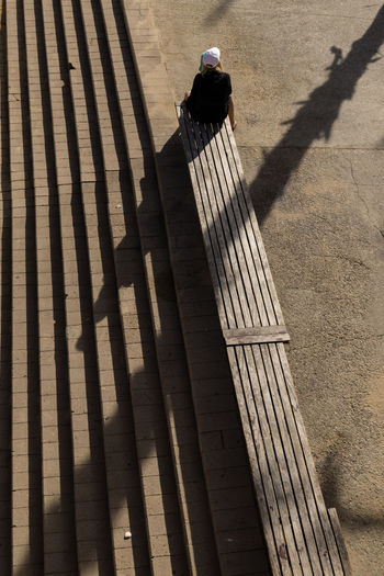 High angle view of woman sitting on bench during sunny day