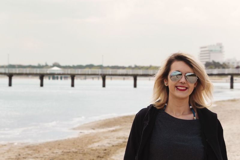 Portrait of smiling woman in sunglasses against sea