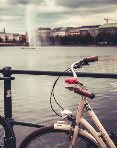 Bicycle on railing by river in city