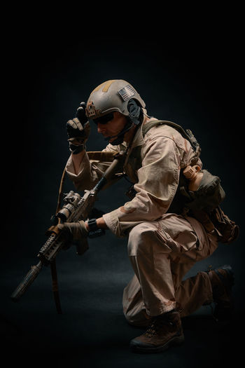 special forces soldier of the united states poses with a rifle on a black background Soldier Uniform Warrior Adult Army Army Soldier Assault Rifles Black Background Combat Helmet Night One Person Outdoors People Special Forces Standing Studio Shot War Weapon Young Adult
