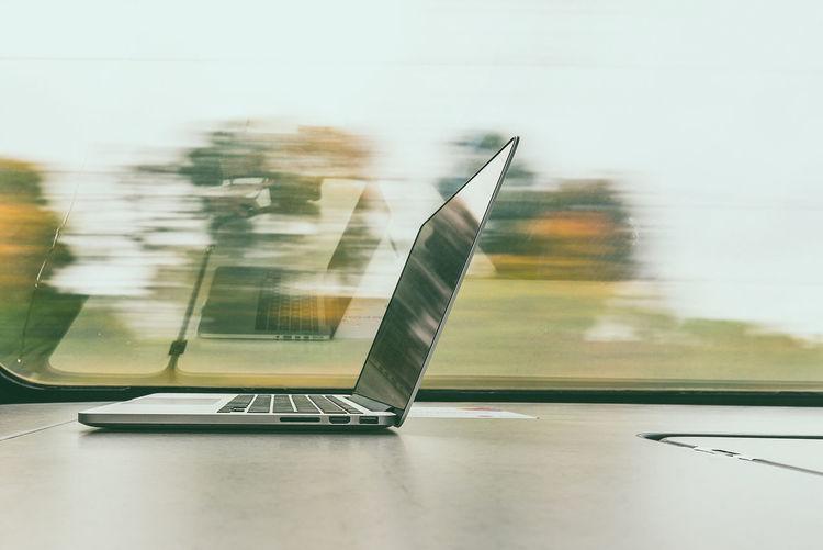 Laptop on table by train window
