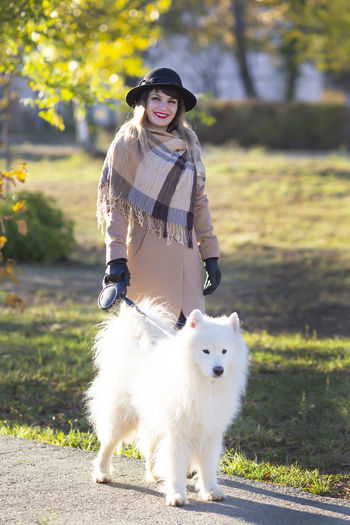 Portrait of woman with dog at park