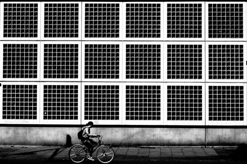 Man riding bicycle on window of building