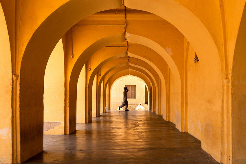 Young man walking under the arches of a mosque in Karnataka, India. Arch Arches Architecture Built Structure Composition Corridor Day Diminishing Perspective Full Length Illuminated India Islam Karnataka Leisure Activity Lifestyles Madrasa Mosque One Person The Way Forward Tunnel Unrecognizable Person Vanishing Point Walking Walkway Yellow