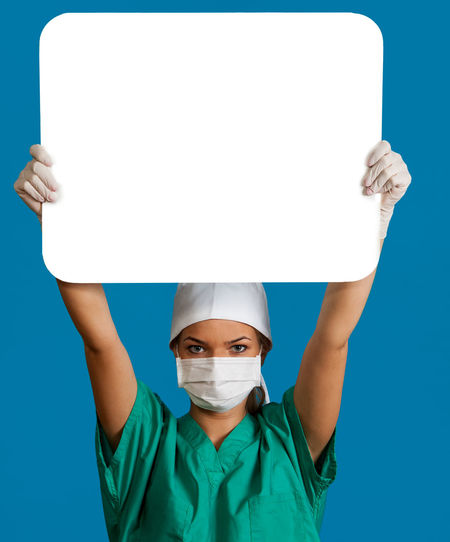 Young woman doctor keeping a white board, against a blue background. Copy Space Doctor  Healthcare Medicine Nurse White Board Blue Blue Background Bonnet Cap Front View Healthcare And Medicine Keeping Mask Medical Cannabis Message One Person People Physician Portrait Real People Studio Shot Surgical Mask Young Adult Young Women