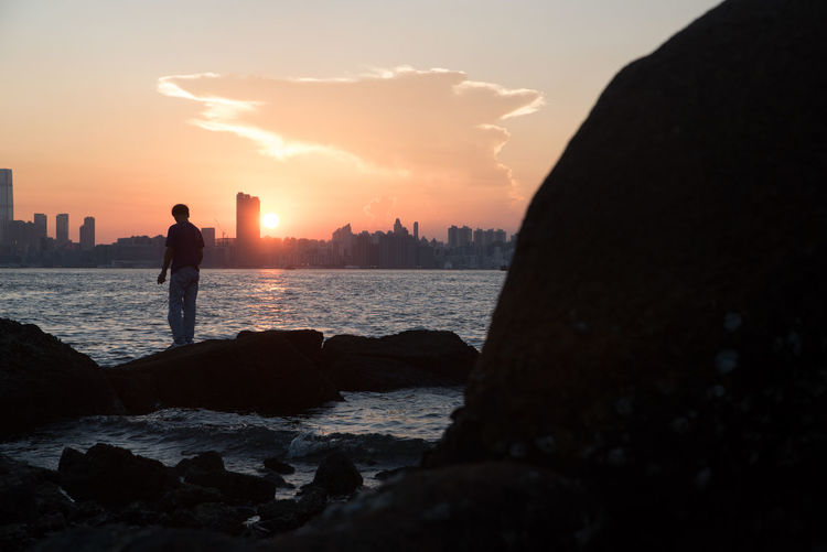 Beauty In Nature Day Full Length Leisure Activity Lifestyles Men Nature Outdoors People Real People Rock - Object Scenics Sea Silhouette Sky Standing Sunset Two People Water