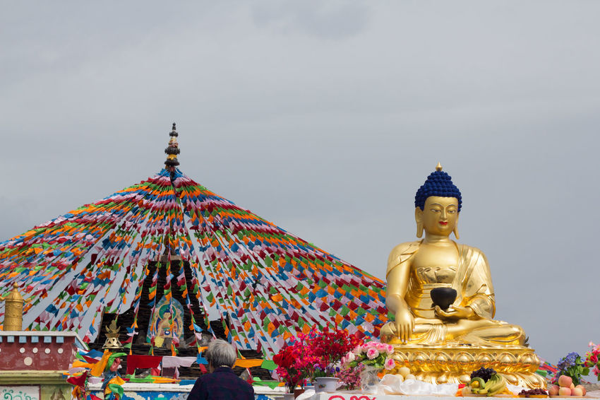 Tibetan Buddhism Tibetan Buddhist Temple Day Golden Color Human Representation Idol Low Angle View Male Likeness No People Outdoors Place Of Worship Religion Sculpture Sky Spirituality Statue Tibet Tibetan Prayer Flags