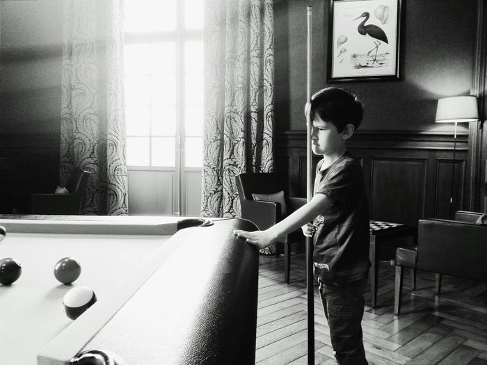 Boy holding cue by pool table at home