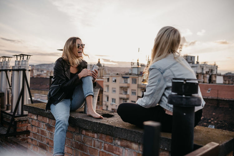 Cheerful Women Talking While Sitting On Building Terrace Against Sky