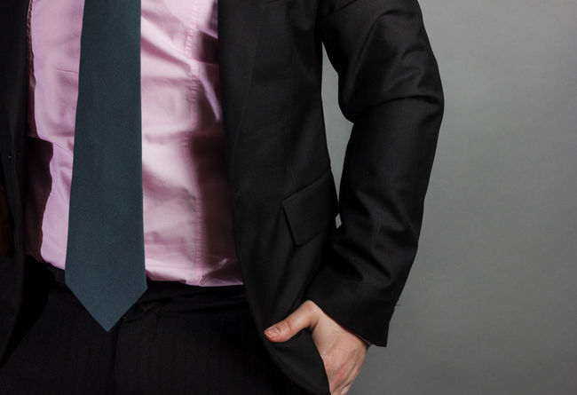 businessman with tie and suit insert hand in trouser pocket in front of grey background Man Office Business Businessman Hand In Pocket Idle Male Occupation Pocket  Suit Tie Trousers Unemployed Unmotivated