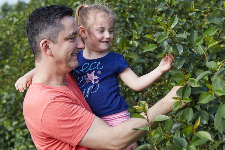 Smiling father with daughter touching plants at agricultural field