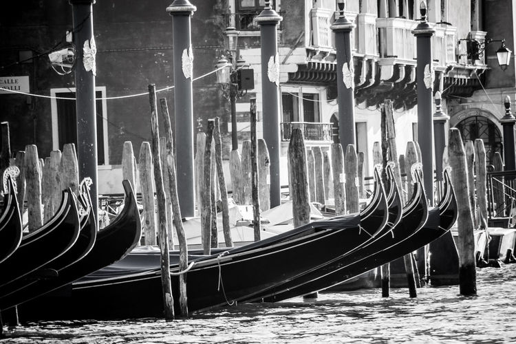 Gondolas moored in grand canal against building on sunny day
