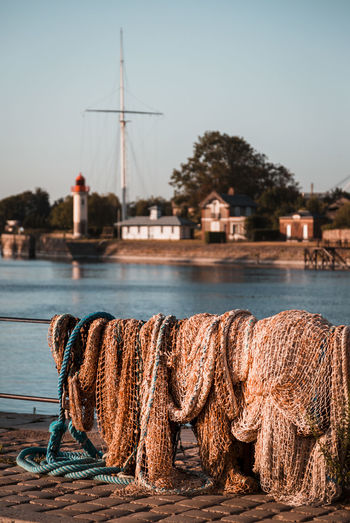 Fishing net at harbor against clear sky during sunset