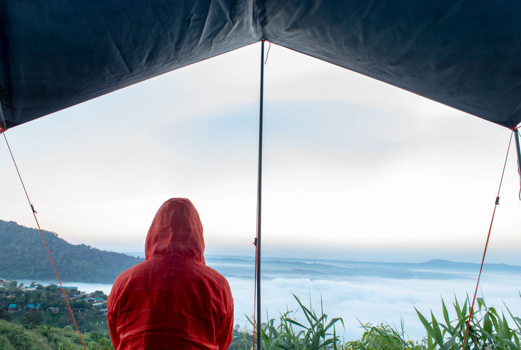 Rear view of man in tent against sky
