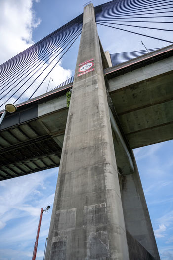 Low angle view of bridge against cloudy sky