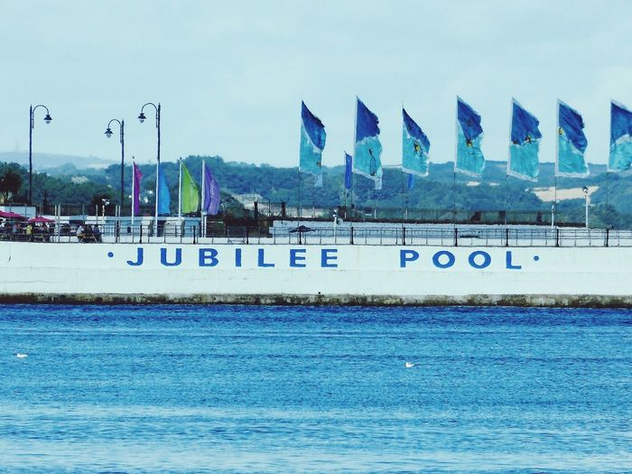 The Jubilee pool Swimming Swimming Pool Outdoor Swimming Pool Calm Sea Sea Sea Water Pool Blue Sea Calm Calm Day Water Modern Sky Architecture Building Exterior Western Script Signboard Amusement Park Ride Poolside