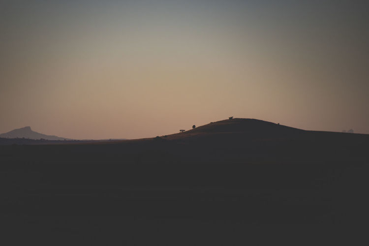 Scenic view of silhouette mountain against clear sky at sunset