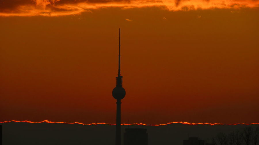 Silhouette of communications tower during sunset