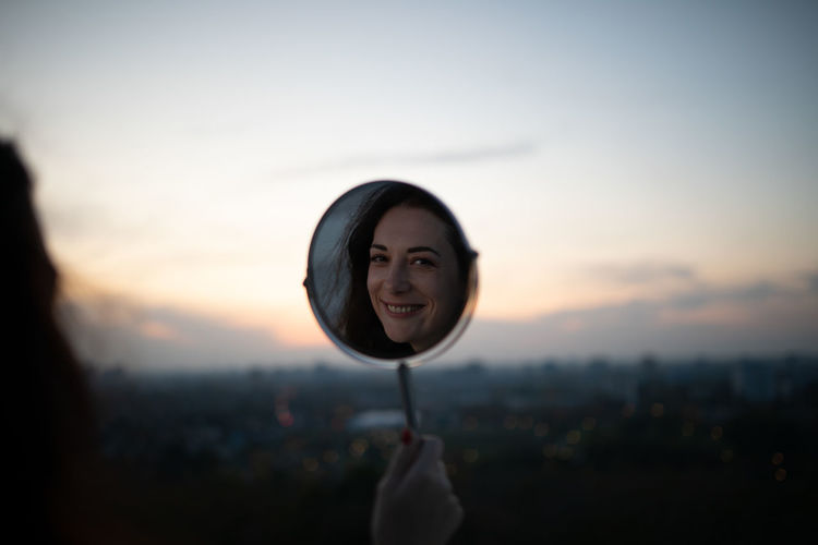 Reflection of smiling woman in mirror against sky during sunset